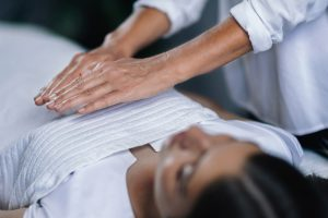 A young woman receiving a reiki healing session.