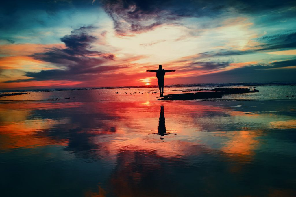 Silhouette of person with arms open to a sunset or sunrise.