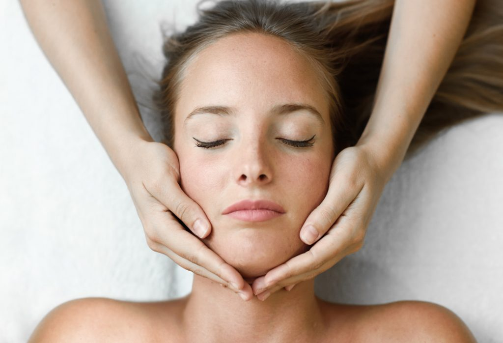 Women with eyes closed lying down with hands wrapped around her face.