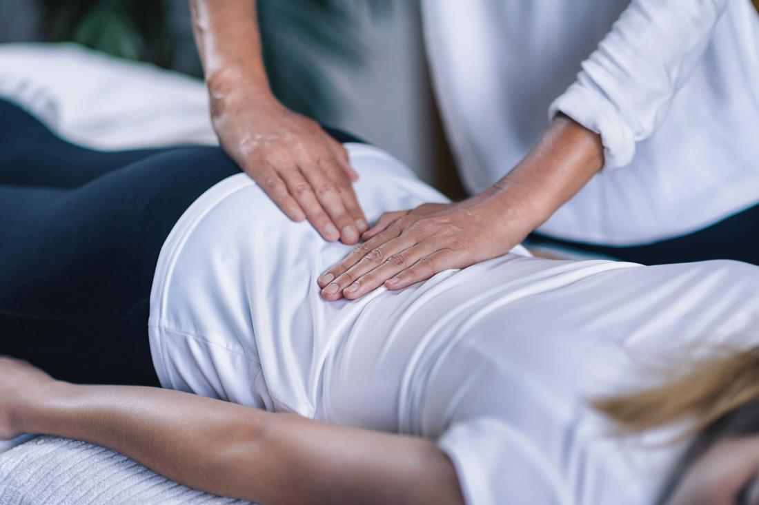 Reiki practicioner holding hands over clients lower back.