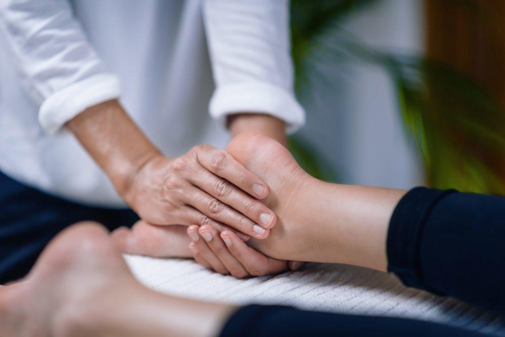 Reiki practioncer gently holding foot during session.